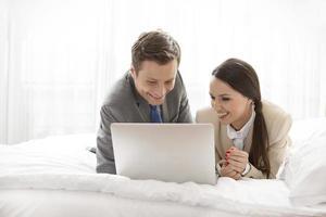couple d'affaires heureux utilisant un ordinateur portable dans la chambre d'hôtel photo