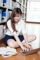 belle étudiante asiatique étudiant dans la bibliothèque avec ordinateur portable photo