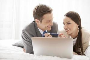 couple d'affaires ludique avec ordinateur portable dans la chambre d'hôtel photo