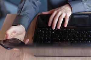 gros plan de l'homme à l'aide d'un ordinateur portable et d'un téléphone mobile. photo