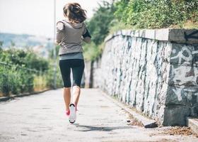 fitness jeune femme jogging dans le parc de la ville. vue arrière photo