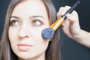 maquilleuse faisant maquillage pour belle femme de race blanche photo