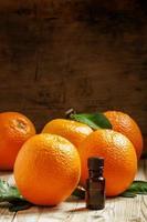 huile d'orange dans une petite bouteille et fruits frais photo