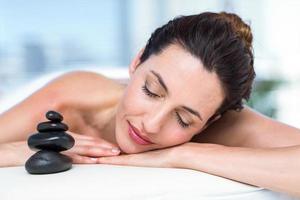 brunette souriante relaxante sur la table de massage photo
