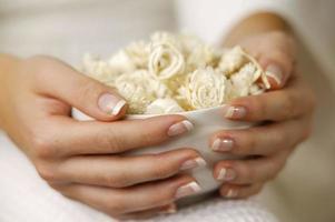 mains manucurées de femme tenant un bol de fleurs