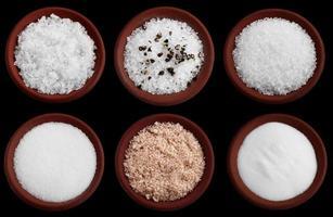 six assiettes en terre cuite avec différents sels de mer sur fond noir photo