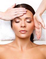 massage du visage. gros plan d'une jeune femme en cure thermale. photo