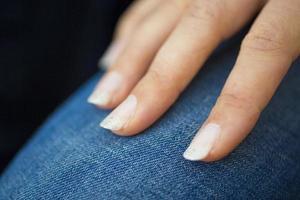 Main de femme caucasienne avec du vernis à ongles de couleur claire photo