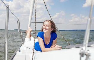 concepts de voyage: femme caucasienne positive souriante sur yacht blanc photo
