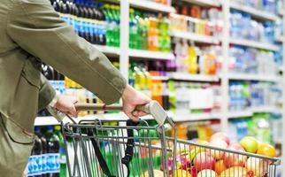 homme caucasien poussant un chariot plein dans un supermarché