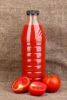 jus de tomate en bouteille sur fond d'un sac