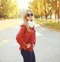 Mode femme blonde portant des lunettes de soleil et une veste en cuir rouge
