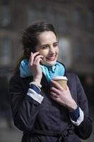 femme heureuse sur téléphone portable à l'extérieur en ville. photo