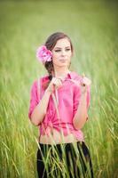 jeune fille en rose sur le champ de blé doré