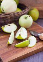 pomme verte tranchée sur une planche à découper en bois