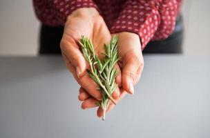 gros plan sur jeune femme au foyer montrant frais rosmarinus