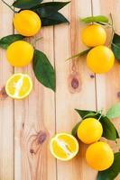 oranges avec des feuilles sur une surface en bois photo