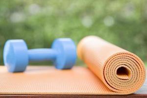 tapis de yoga orange et haltère bleu