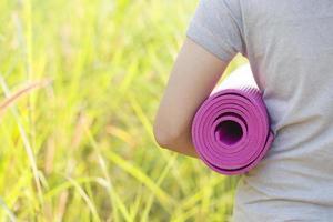 jeune femme tenant un tapis de yoga