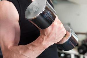 sport - l'homme exerce avec haltères dans la salle de gym photo