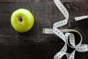 une pomme entourée d'un ruban à mesurer sur mesure en bois