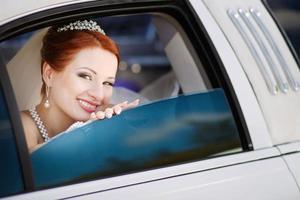 jeune mariée caucasienne souriante en limousine blanche. photo