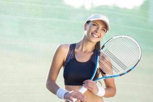 Jolie et heureuse jeune joueuse de tennis caucasienne photo