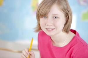 vraies personnes: caucasienne petite fille étudie l'apprentissage à l'école photo