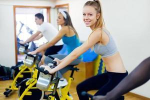 jeunes avec vélo de fitness dans la salle de gym. photo