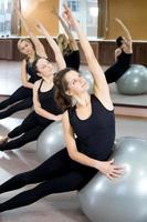 groupe de jeunes femmes s'entraînent sur des balles de pilates