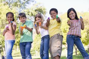 cinq jeunes amis avec des pistolets à eau en plein air souriant photo