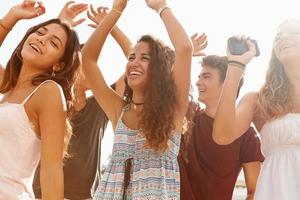 groupe d'amis adolescents dansant en plein air contre le soleil photo
