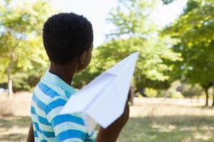 mignon petit garçon avec avion en papier photo