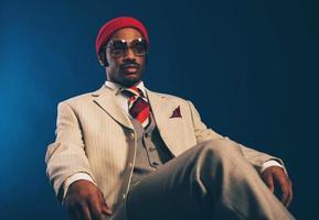 Homme afro pensif en tenue de soirée assis sur une chaise photo