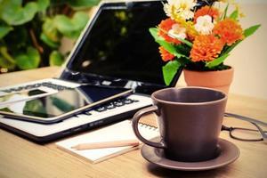 ordinateur portable et tasse de café avec fleur sur le bureau photo