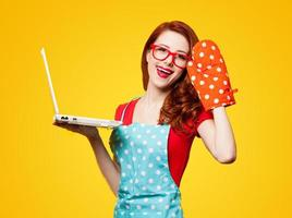 jeune femme au foyer avec ordinateur et gants de cuisine