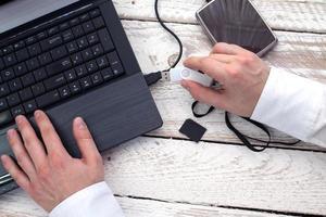 la main de l'homme met la clé USB dans l'ordinateur portable. photo