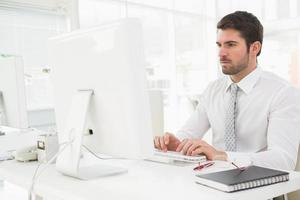 homme d'affaires concentré tapant sur le clavier
