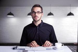 Image composite d'homme d'affaires concentré en tapant sur le clavier photo