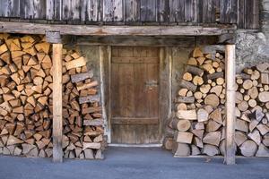bois de chauffage empilé à l'extérieur de la porte de la grange.