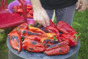homme méconnaissable rôtir les poivrons rouges. photo