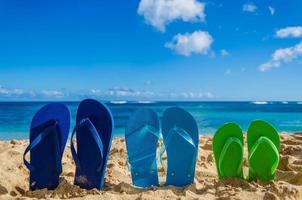 tongs colorées sur la plage de sable photo