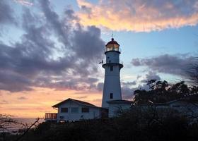 phare au milieu du ciel coucher de soleil photo