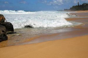 pierres de lave sur la plage de coucher du soleil photo