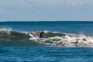 combinaison surfeuse noire surfant sur la vague