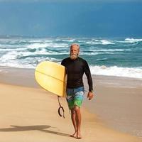 surfeur à la mer est debout avec une planche de surf