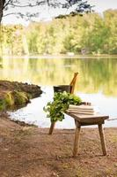 paysage d'été finlandais et objets sauna sur banc au bord du lac.