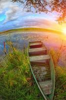 bateau en roseaux sur le lac au coucher du soleil