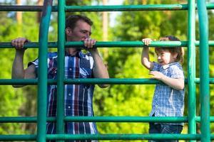 père et fils jouant sur l'aire de jeux.