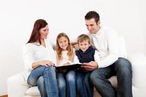 heureux jeune famille regardant l'album photo